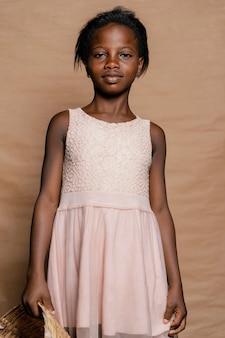 Młoda dziewczyna stoi z koszem ze słomy