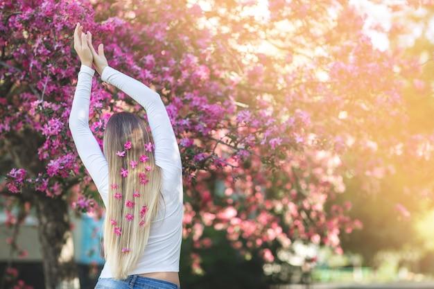 Młoda dziewczyna stoi z powrotem do aparatu na tle kwiatów z kwiatami we włosach