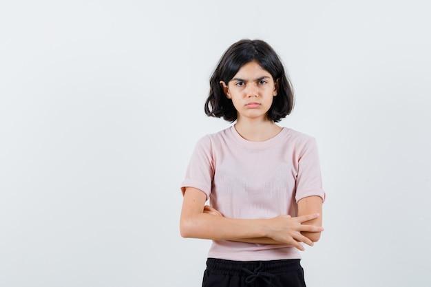 Młoda dziewczyna stoi z rękami skrzyżowanymi w różowej koszulce i czarnych spodniach i wygląda poważnie