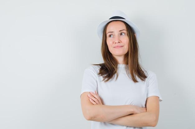 Młoda dziewczyna stoi ze skrzyżowanymi rękami w białym kapeluszu t-shirt i marzycielski wygląd