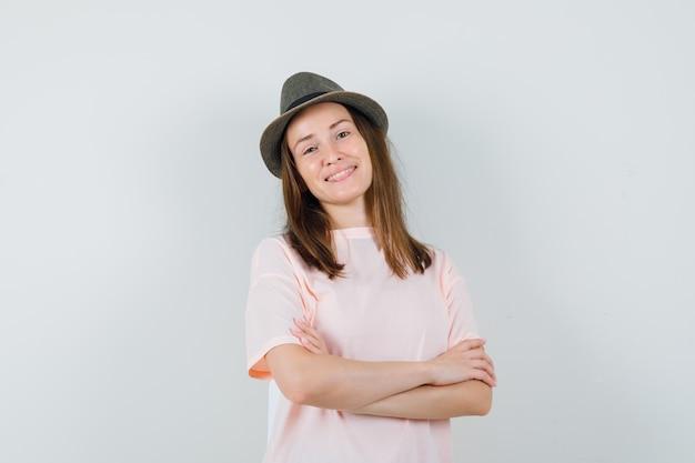 Młoda dziewczyna stoi ze skrzyżowanymi rękami w różowym kapeluszu t-shirt i wygląda optymistycznie