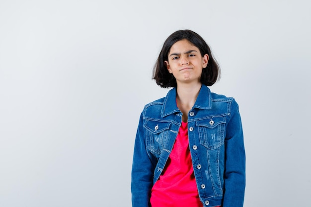 Młoda dziewczyna stojąc prosto i pozowanie na kamery w czerwonej koszulce i kurtce dżinsowej i patrząc poważnie.