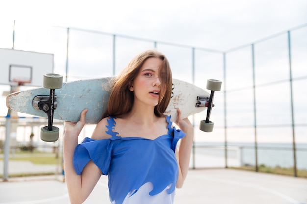 Młoda dziewczyna stojąc z deskorolką i patrząc na kamery na zewnątrz na placu zabaw