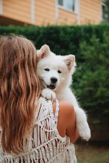 Młoda dziewczyna stojąc z powrotem trzymając szczeniaka samojeda w ręce na zewnątrz. posiadanie koncepcji zwierzaka. koncepcja słodkie zwierzęta.