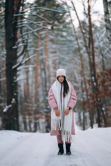 Młoda dziewczyna stojąca na środku zaśnieżonej drogi