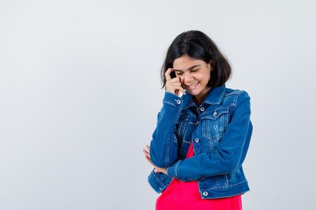 Młoda dziewczyna stojąca w myśleniu pozie w czerwonej kurtce t-shirt i dżinsowej i patrząc zamyślony, widok z przodu.