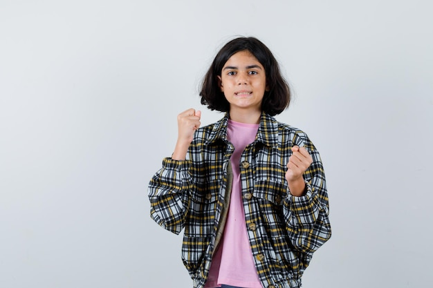 Młoda dziewczyna stojąca w pozie boksera w kraciastej koszuli i różowej koszulce i patrząc zły. przedni widok.