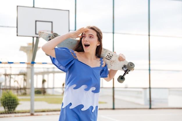 Młoda dziewczyna stojąca z deskorolką patrząc na coś na zewnątrz na placu zabaw