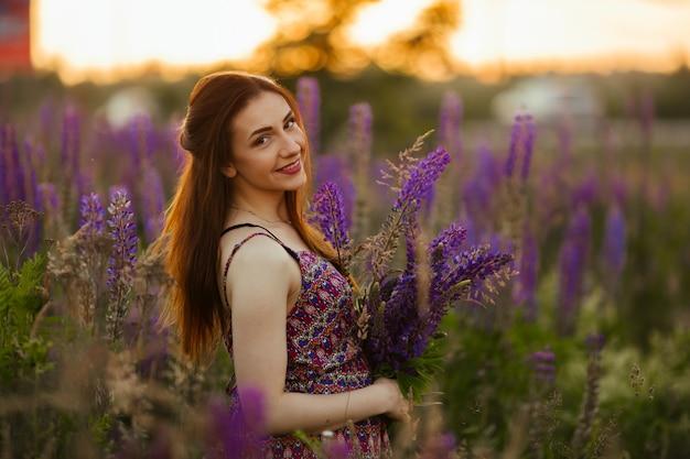 Młoda dziewczyna stojak w polu przegapia lawendy pole. uśmiechnięta beztroska caucasian dziewczyna w sukni cieszy się zmierzch