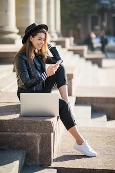 Młoda dziewczyna student businesswoman pracuje z laptopem swojej marki w centrum miasta