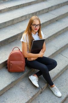 Młoda dziewczyna student gir siedzi na schodach, przygotowując się do egzaminów na zewnątrz
