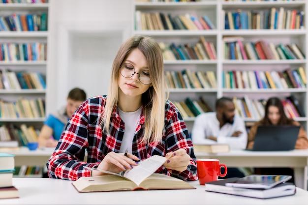 Młoda dziewczyna studentka, ubrana w swobodną kraciastą koszulę i okulary, siedząca przy stole w bibliotece i czytająca książkę, przygotowująca się do testu lub egzaminu