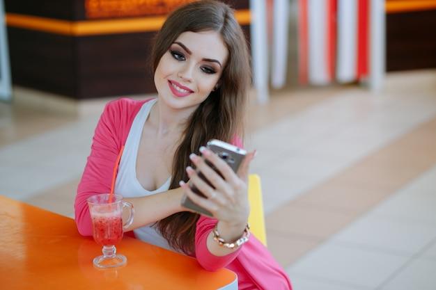 Młoda dziewczyna stwarzających z telefonem i sody
