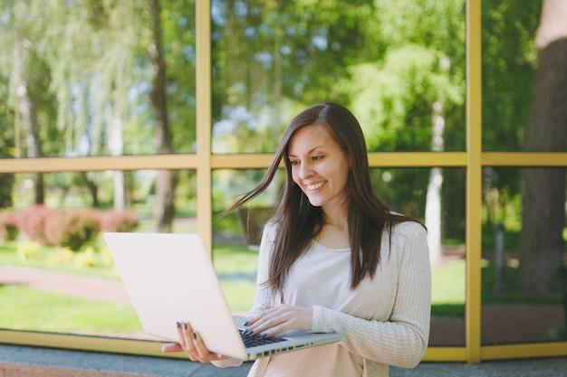 Młoda dziewczyna sukcesy w lekkich ubraniach casual. piękna kobieta pracuje na nowoczesnym komputerze przenośnym w pobliżu budynku lustro z odbiciem drzewa na ulicy na zewnątrz. biuro mobilne. koncepcja biznesowa freelancer