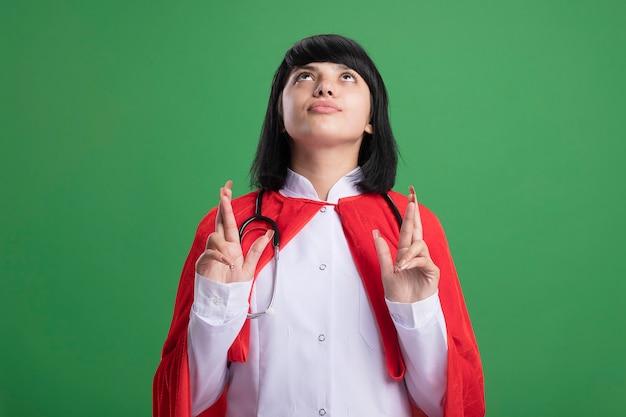Młoda dziewczyna superbohatera patrząc na sobie stetoskop z płaszczem medycznym i peleryną skrzyżowanymi palcami na białym tle na zielono