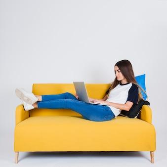 Młoda dziewczyna surffing sieci web na kanapie