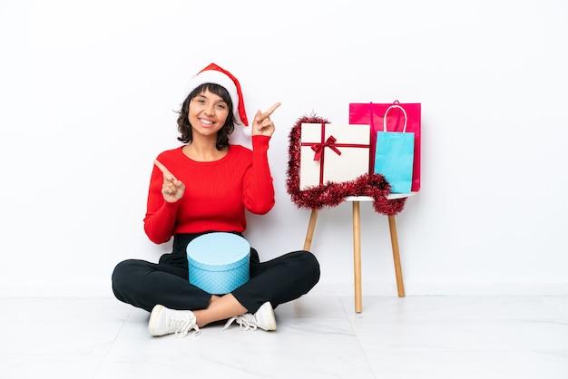Młoda dziewczyna świętująca boże narodzenie siedzi na podłodze na białym tle na białym bakcground wskazując palcem na boki i szczęśliwa