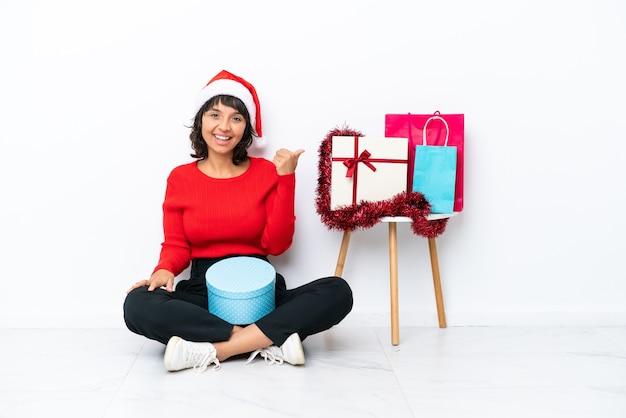Młoda dziewczyna świętująca boże narodzenie siedzi na podłodze na białym tle na białym tle, wskazując na bok, aby zaprezentować produkt