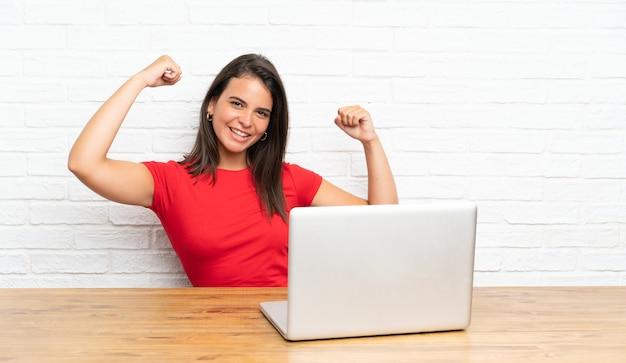 Młoda dziewczyna świętuje zwycięstwo z komputerem osobistym w stole