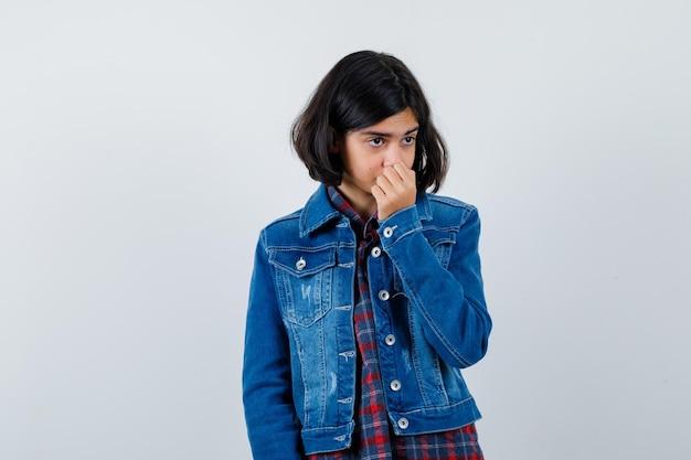 Młoda dziewczyna szczypie nos z powodu nieprzyjemnego zapachu w kraciastej koszuli i dżinsowej kurtce i wygląda na zirytowaną