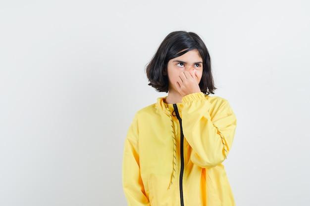 Młoda dziewczyna szczypie nos z powodu nieprzyjemnego zapachu w żółtej bomberce i wygląda na zirytowaną.