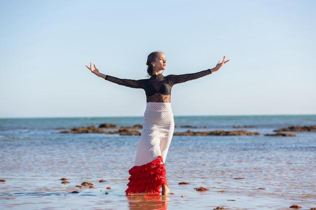 Młoda dziewczyna tańczy flamenco na aguan na plaży w typowym stroju andaluzyjskim