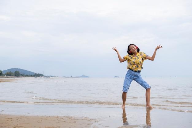 Młoda dziewczyna, taniec i słuchanie muzyki na pięknej plaży