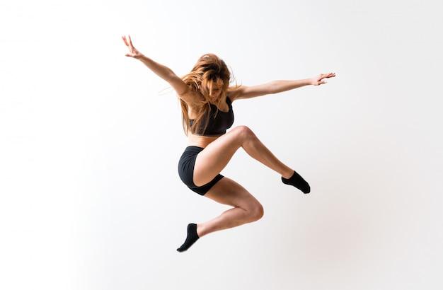 Młoda dziewczyna taniec na białym tle ściany