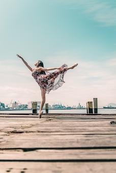 Młoda dziewczyna taniec na boardwalk w nabrzeżu
