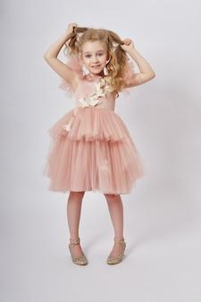 Młoda dziewczyna tęskni za pięknem w pięknej sukience. kosmetyki i makijaż dla dzieci. dziewczyna pozuje na świetle. śmieszne emocje i niespodzianka. ,
