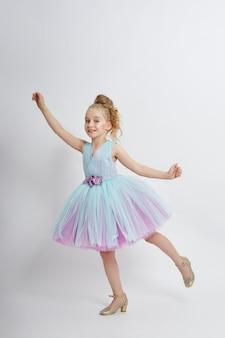 Młoda dziewczyna tęskni za pięknem w pięknej sukience. kosmetyki i makijaż dla dzieci. dziewczyna pozuje