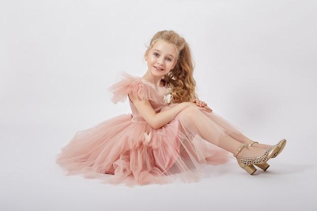 Młoda dziewczyna tęskni za pięknem w pięknej sukience. kosmetyki i makijaż dla dzieci