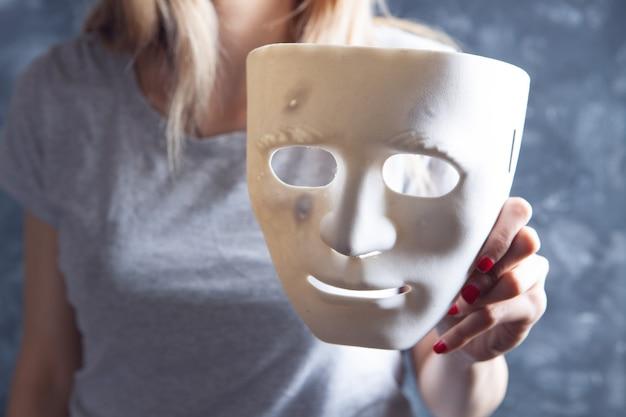 Młoda dziewczyna trzyma anonimową maskę