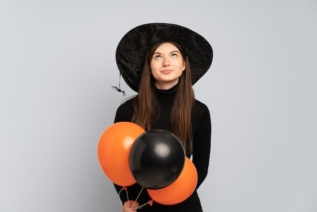 Młoda dziewczyna trzyma balony z czarnym kapeluszem i czarną sukienką