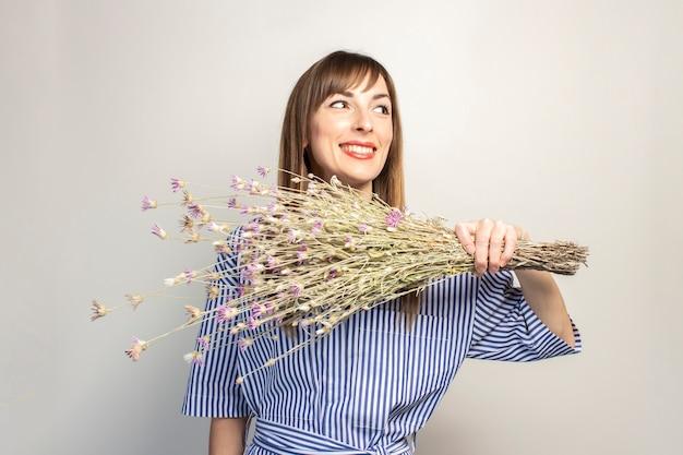 Młoda dziewczyna trzyma bukiet polnych kwiatów, dziewczyna pokazuje emocje na jasnej powierzchni