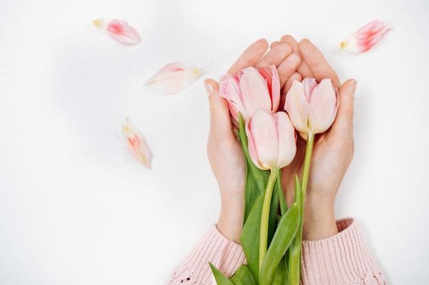 Młoda dziewczyna trzyma bukiet różowych tulipanów. widok z góry, białe tło, miejsce na tekst.