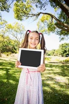 Młoda dziewczyna trzyma cyfrową pastylkę w parku