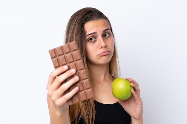 Młoda dziewczyna trzyma czekoladę i jabłko