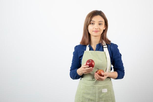 Młoda dziewczyna trzyma czerwone jabłka na białym tle.