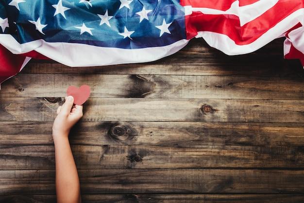 Młoda dziewczyna trzyma czerwone serce karty w ręce na amerykańskiej flagi