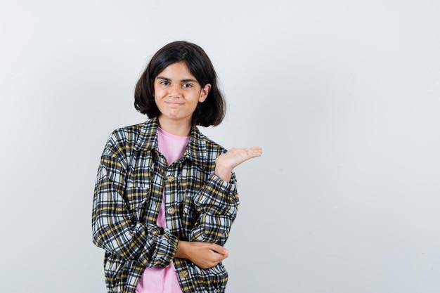 Młoda dziewczyna trzyma dłoń na zewnątrz i trzyma jedną rękę na łokciu w kraciastej koszuli i różowej koszulce i wygląda ładnie, widok z przodu.