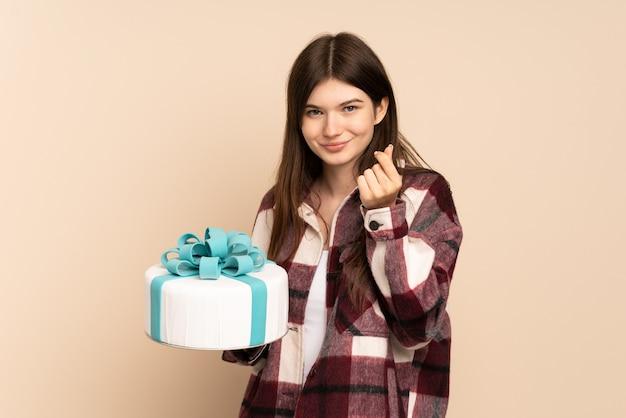 Młoda dziewczyna trzyma duży tort na białym tle na beżu zarabianie pieniędzy gest