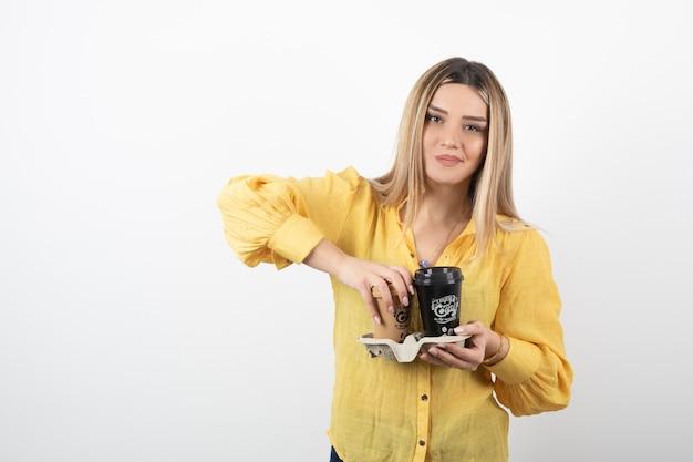 Młoda dziewczyna trzyma filiżanki kawy na białym tle.