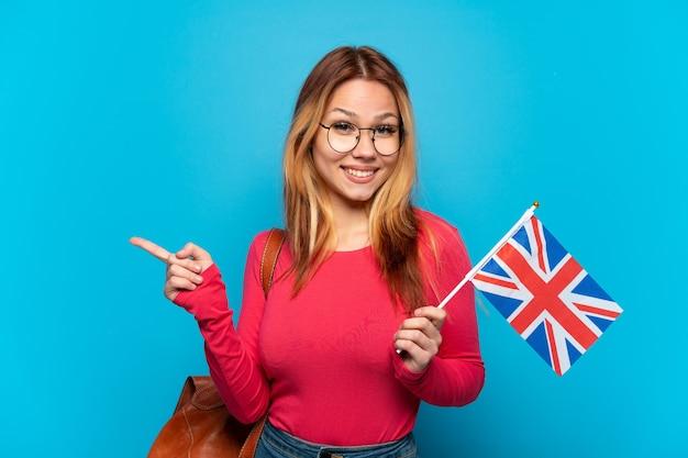 Młoda dziewczyna trzyma flagę wielkiej brytanii na białym tle, wskazując palcem w bok