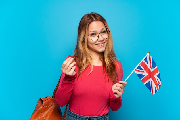 Młoda dziewczyna trzyma flagę zjednoczonego królestwa na izolowanych niebieskim tle zarabiania pieniędzy gestu