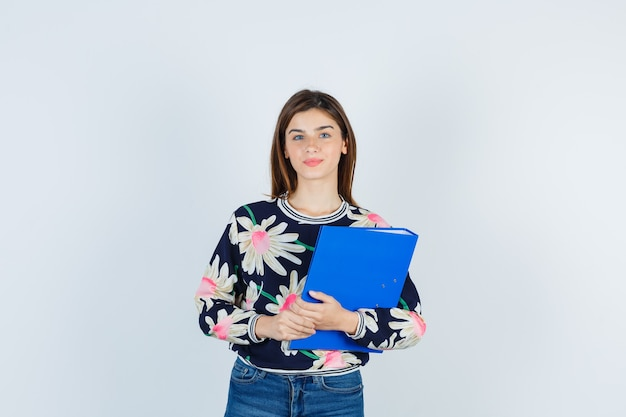 Młoda dziewczyna trzyma folder, patrząc na kamery w kwiatowy bluzka, dżinsy i patrząc ładny, widok z przodu.