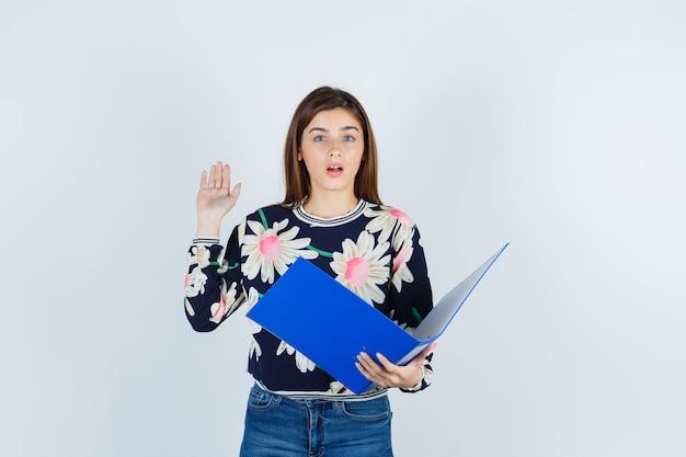 Młoda dziewczyna trzyma folder, podnosząc dłoń w kwiecistej bluzce, dżinsach i patrząc w szoku, widok z przodu.