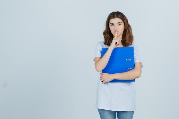 Młoda dziewczyna trzyma folder, pokazując gest ciszy w białej koszulce i patrząc pewnie. przedni widok.