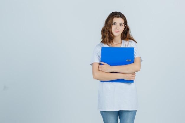 Młoda dziewczyna trzyma folder w białej koszulce i wygląda rozsądnie, widok z przodu.