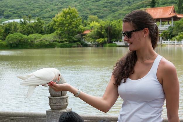 Młoda dziewczyna trzyma gołębia na ona ręki